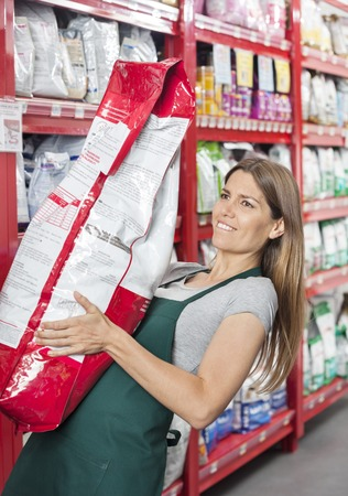 saleswoman: Mid adult saleswoman carrying heavy food package in pet store Stock Photo