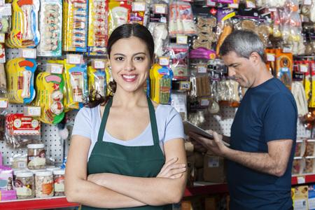Portret van vertrouwen verkoopster met de armen gekruist staan terwijl de klant het selecteren van het product in de winkel