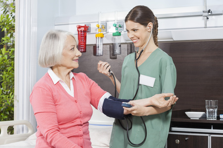 senior female: Smiling female nurse examining blood pressure of senior patient in rehabilitation center