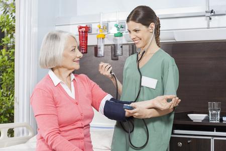 senior lady: Smiling female nurse examining blood pressure of senior patient in rehabilitation center