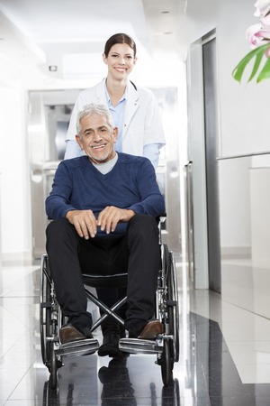 rehab: Portrait of happy female doctor pushing senior patient in wheelchair at rehab center Stock Photo