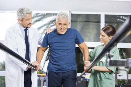 Male and female physiotherapists motivating senior man to walk between parallel bars in fitness studio