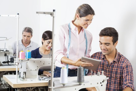 modiste: Male and female tailors using digital tablet at workbench in sewing factory