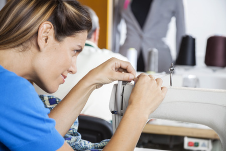 threading: Side view of smiling female tailor threading needle of sewing machine at factory Stock Photo