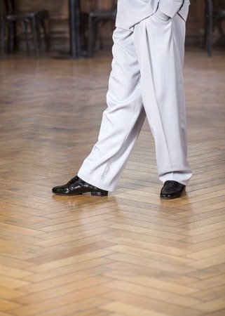 trouser legs: Low section of male dancer performing on hardwood floor at restaurant
