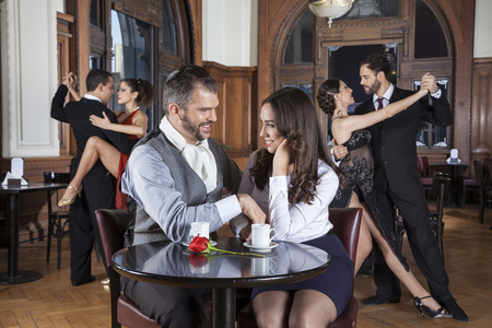 Happy couple looking at each other while dancers performing tango in restaurant