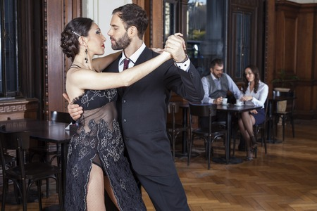 argentina dance: Passionate dancers doing tango while mid adult couple dating in restaurant Stock Photo