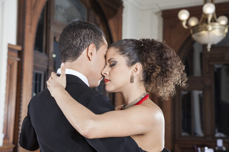 closed club: Beautiful young woman and man touching foreheads while performing tango in restaurant