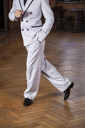 trouser legs: Low section of male tango dancer performing cross step on hardwood floor in restaurant