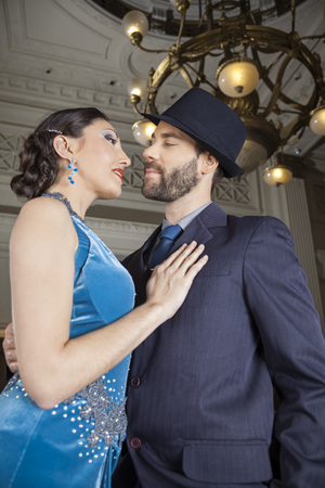mid adult male: Low angle view of passionate mid adult male and female dancers performing tango in cafe