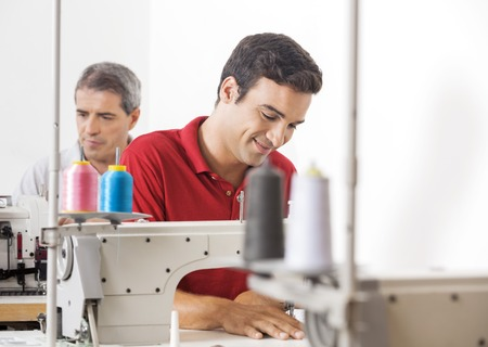 modiste: Smiling male tailor using sewing machine at factory with colleague in background