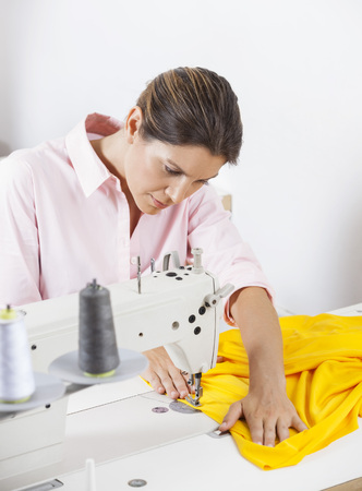 modiste: Female tailor stitching yellow fabric at workbench in factory