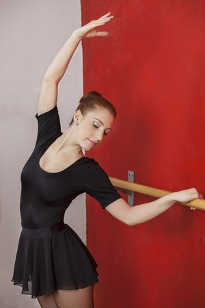 barre: Female ballet dancer stretching at barre in dance studio