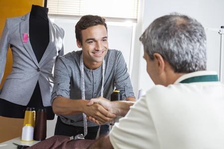 sastre masculino feliz agitando la mano con su colega en la mesa de trabajo en la fábrica de costura