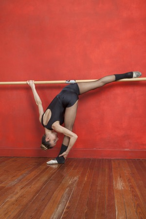 barre: Full length of young female ballet dancer practicing at barre in studio Stock Photo