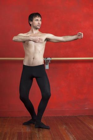 ballet hombres: Longitud total de bailarín de sexo masculino sin camisa que practica en estudio de ballet