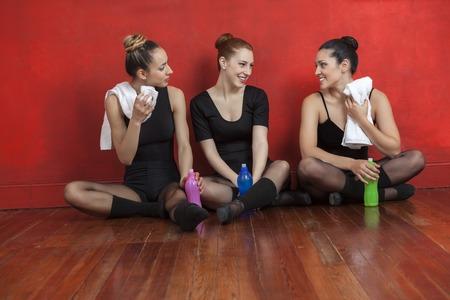 ballet bar: Tired ballet dancers sitting together on hardwood floor in training studio
