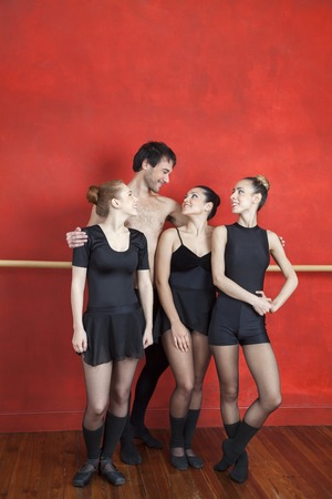 arms around: Smiling mid adult trainer standing arms around ballerinas in studio