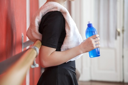 barre: Midsection side view of ballerina holding waterbottle in dance studio Stock Photo