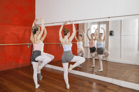 full length mirror: Full length of dancers performing while looking at mirror at ballet studio