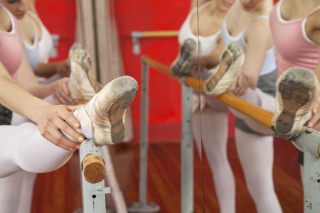 ballet bar: Cropped image of ballerinas with legs on bar performing in dance studio