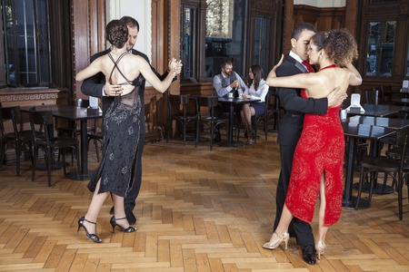 Full length of dancers performing tango while couple dating in restaurant Stock Photo