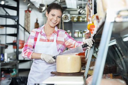 saleswoman: Portrait of smiling young saleswoman slicing whole cheese with double handled knife at counter in shop