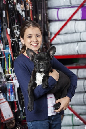 petshop: Portrait of happy girl carrying French Bulldog in pet store