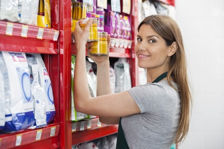 Portrait of confident saleswoman holding food cans by shelves in pet store