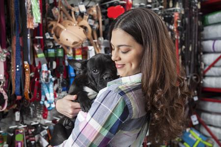 petshop: Smiling beautiful customer hugging French Bulldog in store