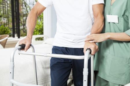 helping: Sección media de enfermera asiste a la mujer mayor con el caminante en el centro de rehabilitación Foto de archivo