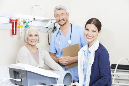 physiotherapists: Portrait of smiling physiotherapists and female patient at rehab clinic Stock Photo