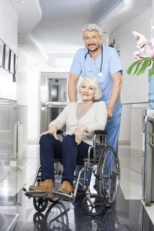 long term care services: Portrait of mature physiotherapist pushing senior woman in wheelchair at rehab center
