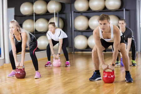 gym class: Full length of determined friends lifting kettlebells in gym Stock Photo