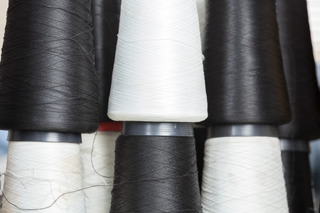 full frame: Full frame shot of black and white thread spools at sewing factory Stock Photo
