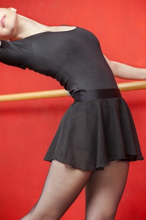 barre: Midsection of female dancer wearing ballet skirt while stretching at barre in studio