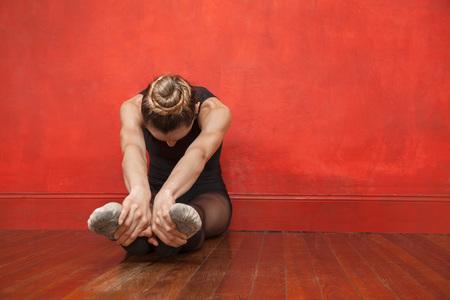 'ballet girl': Full length of female ballet dancer stretching her legs in dance studio