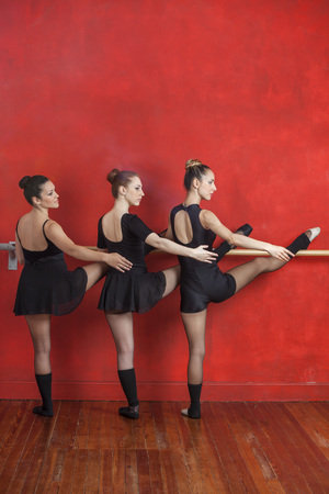 barre: Full length rear view of young ballerinas practicing at barre against red wall in studio