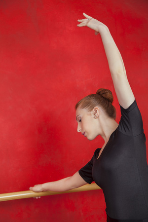 barre: Female ballet dancer with hand raised at barre against red wall in dance studio Stock Photo