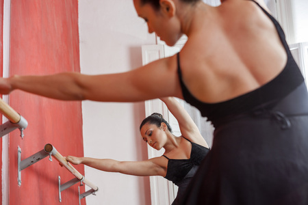 graceful: Rear view of young female ballet dancer performing in front of mirror at studio Stock Photo