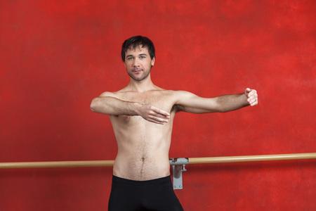 ballet hombres: Retrato de bailarina de ballet masculino practicando sin camisa contra la pared roja en el estudio Foto de archivo