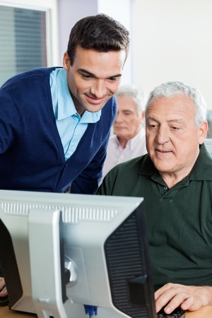 the elderly tutor: Young male teacher assisting senior man in computer class Stock Photo