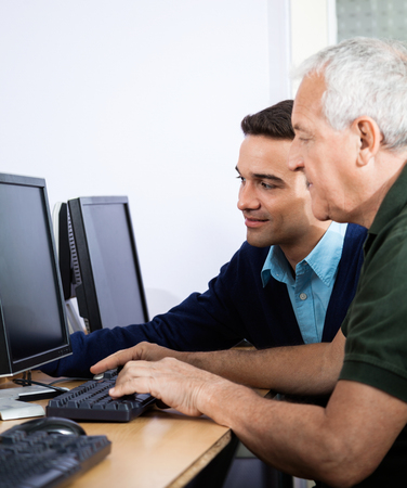 the elderly tutor: Young male teacher assisting senior man in using computer at classroom