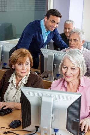 assistant: Senior female classmates using computer at classroom while tutor explaining man in background Stock Photo