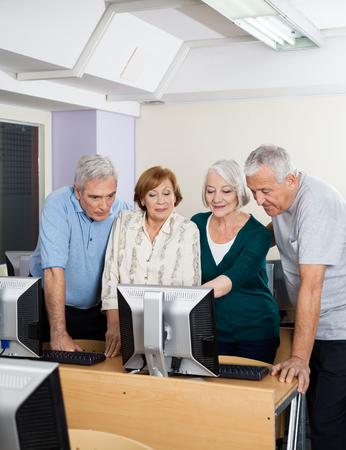 De gelukkige hogere mannen en vrouwen met behulp van de computer in de klas