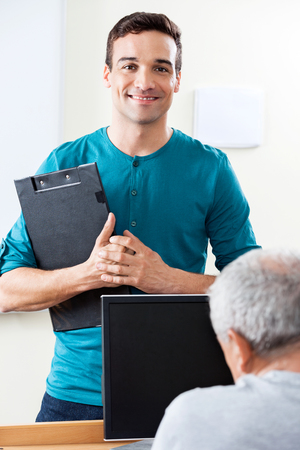 the elderly tutor: Portrait of happy male teacher holding clipboard with male student in computer class Stock Photo