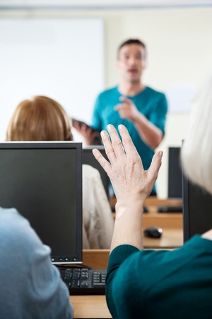 the elderly tutor: Senior woman asking question while tutor explaining in computer class