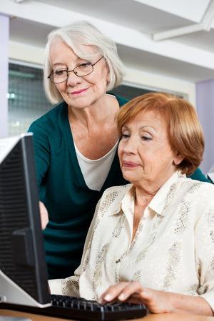 senior woman: Happy senior woman assisting female friend in computer class Stock Photo