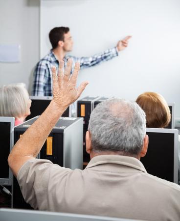 tutor: Hombre mayor que levanta la mano, mientras que el tutor explicando en clase del ordenador