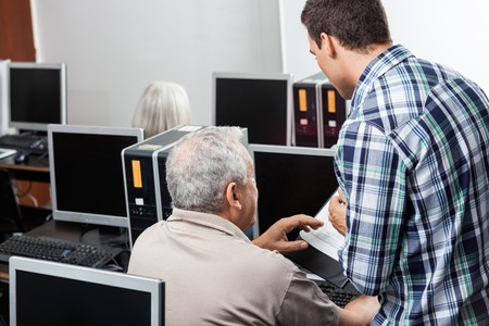 the elderly tutor: Male teacher assisting senior man in using computer at classroom Stock Photo